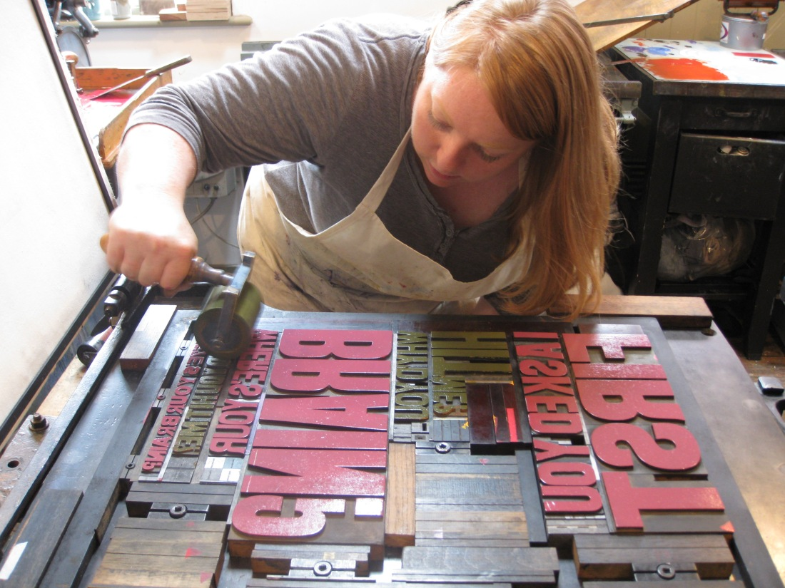 MissGingernut rolling ink on the wooden letters