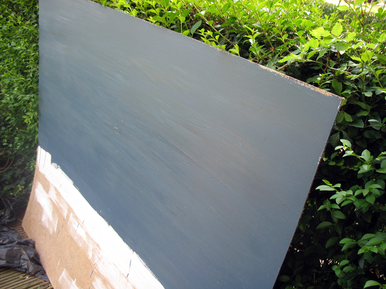 Painting the large board outside in the sun